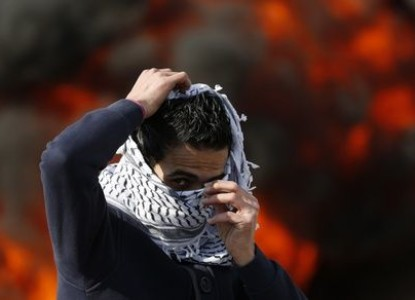 A stone-throwing Palestinian protester adjusts his Keffiyeh during clashes with Israeli soldiers near Ramallah