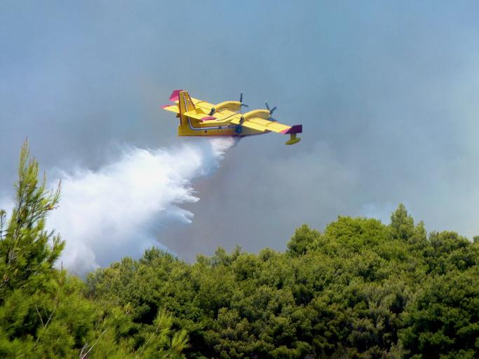 Ciovo, Croatia, August, 2012: Bombardier CL-415 Super Scooper 246 from Croatia makes a water drop on a wildfire in island Ciovo Croatia.