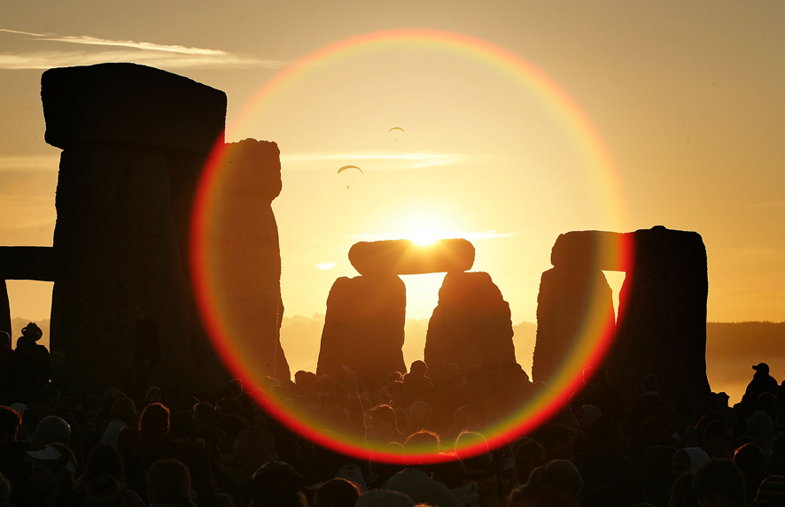 People celebrate the midsummer sun as it rises over the megalithic monument of Stonehenge on June 21, 2005 on Salisbury Plain, England. Crowds gathered at the ancient stone circle to witness the sun rise on the longest day of the year in the Northern Hemisphere.